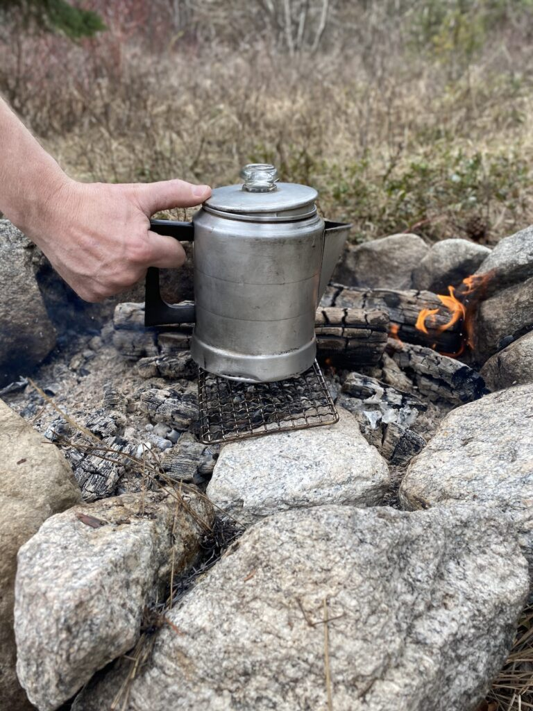 putting a coffee pot on the campfire for coffee or tea