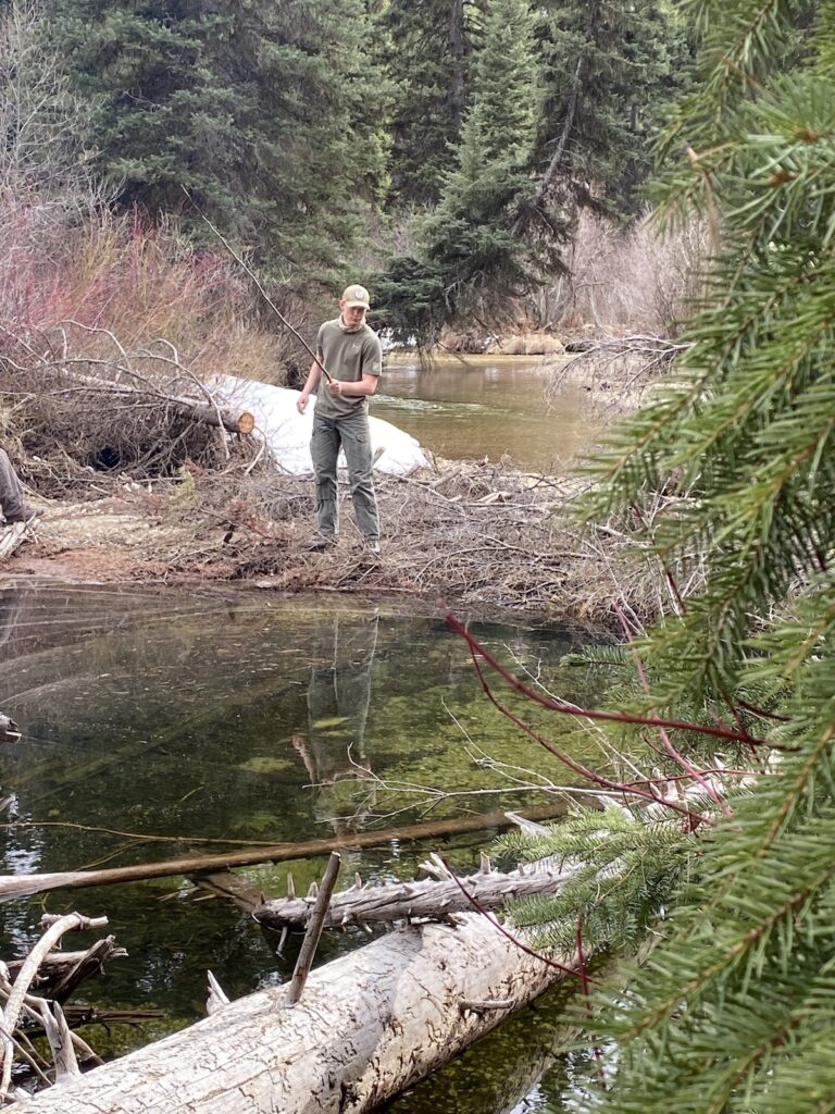 creek fishing in Montana with a willow branch and fishing kit