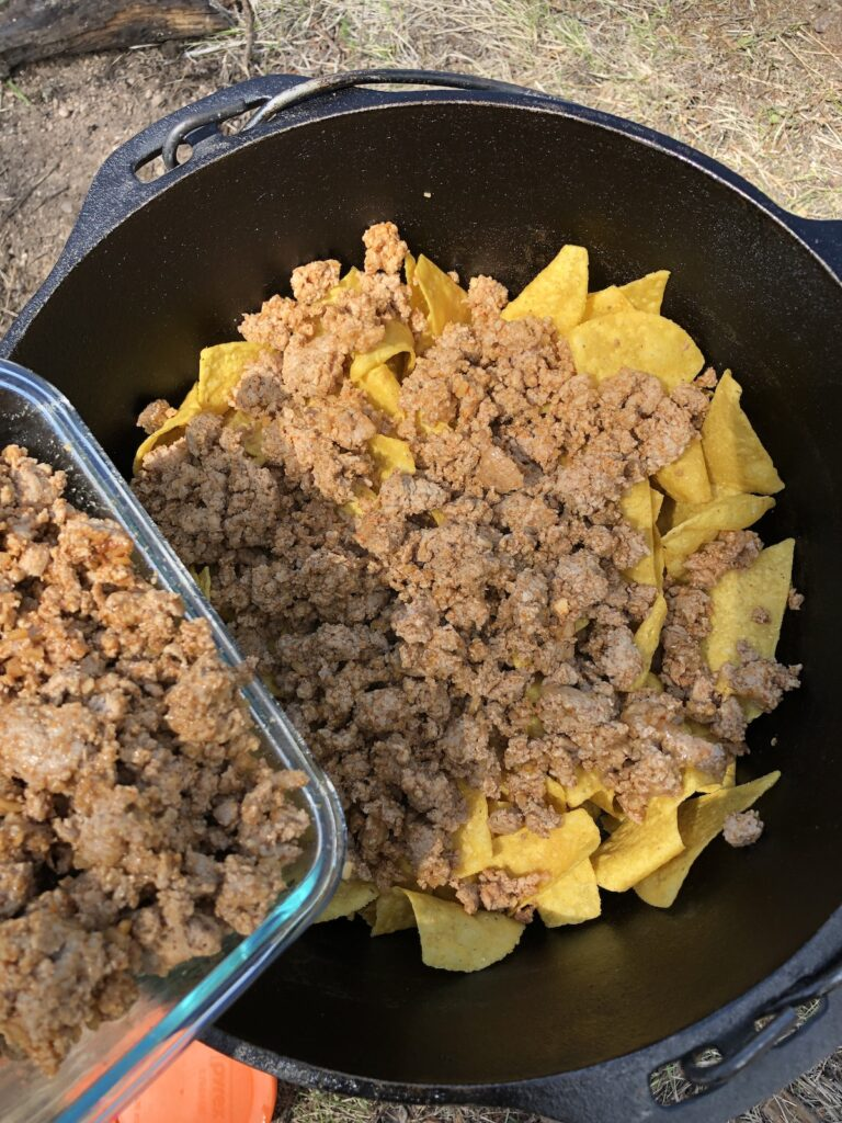adding the precooked taco meat to the campfire nachos