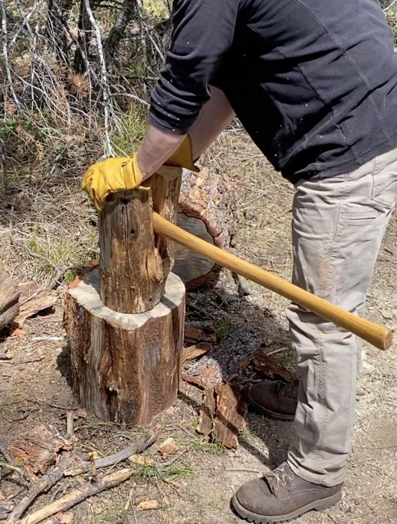 Splitting a Swedish fire log with an ax.