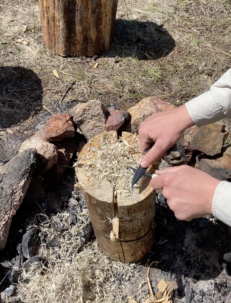 starting a fire with a fire steel on a log