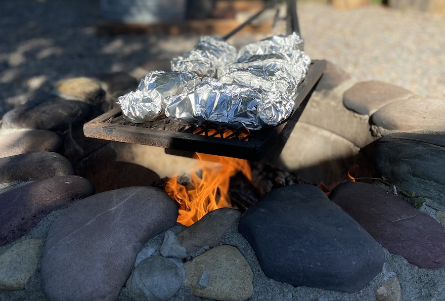 foil packets cooking on a fire